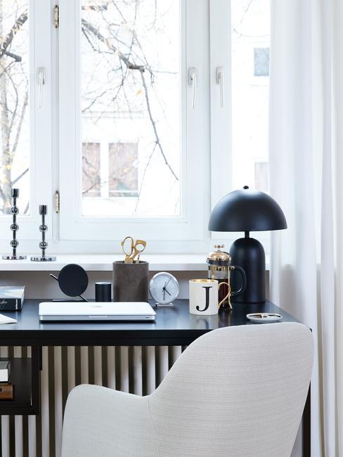 Czarne biurko z lampą, zegarem i innymi akcesoriami stojące przy oknie