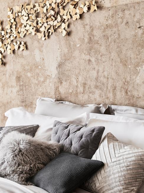 Sypialnia z betonową ścianą, metalowymi dekoracjami oraz łóżkiem z wieloma poduszkami