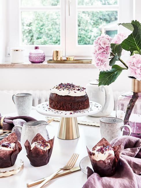 Ciasto czekoladowe na ozdobnej paterze posypanej płatkami kwiatów