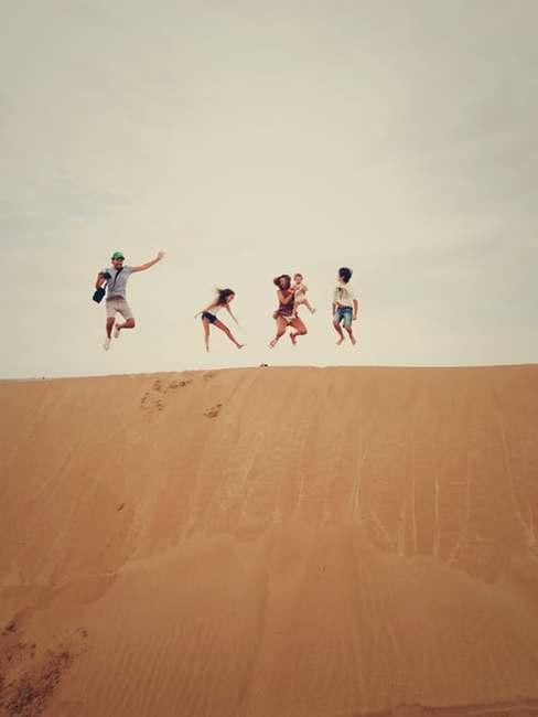 Czteroosobowa rodzina skacząca na wydmach