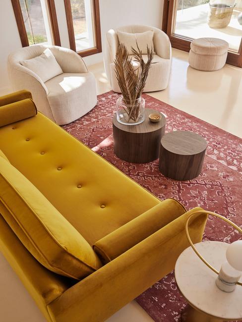 Salon w stylu boho z czerwonym dywanem, sofa w kolorze ochry oraz białymi fotelami