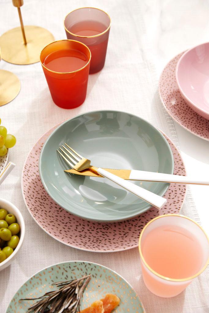 Różowy talerz oraz zielona miska ustawione na zastawionym stole