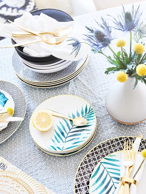 Zastawa kuchenna w stylu ekscentrycznym ustawiona na zastawionym stole obok wazonu z tulipanami