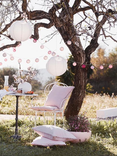 Udekorowany ogród za pomocą lampionów, poduszek oraz girlandy cotton balls