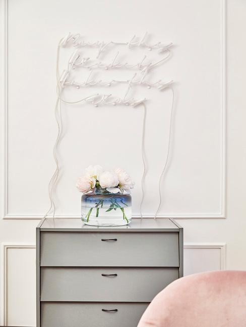 Fragment jasnego salonu z małą komodą oraz baiłymi literami na ścianie