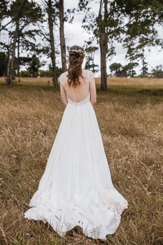 Panna Młoda stojąca tyłem w sukni w stylu boho