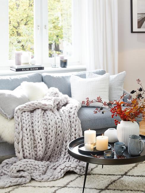 Wnętrze jasnego, przytulnego salonu z niebieska kanapą, dużą ilościa poduszek oraz kocem