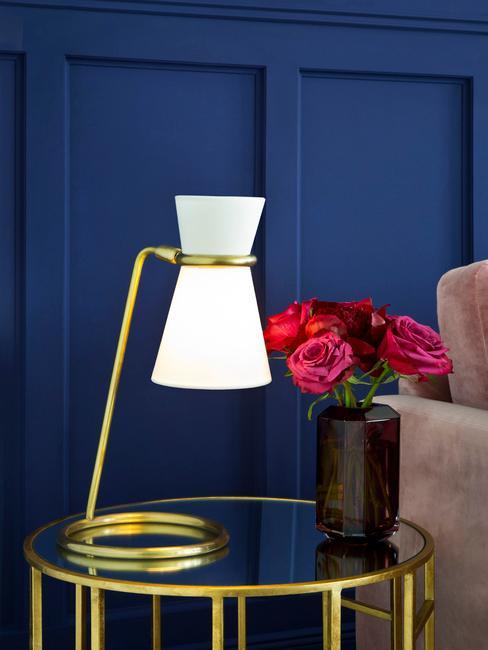 Niebieski salon w którym znajduje się beżowa sofa, szklany stolik z złotą lampką i wazonem żywych kwiatów