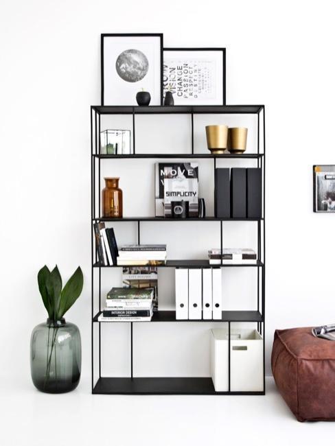 Czarny regał w białym salonie na którym znajdują się książki oraz dekoracje do domu