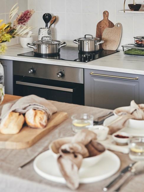 Fragment kuchni z wyspą kuchenną na którym znajduje się pieczywo oraz deska do krojenia