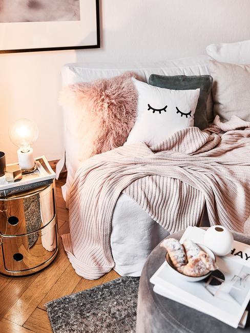 Biała sofa z miękkimi poduszkami, obok złoty stolik pomocniczy