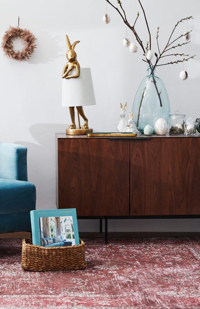 Salon z niebieską sofą, drewnianą komodą oraz ozdobami wielkanocnymi