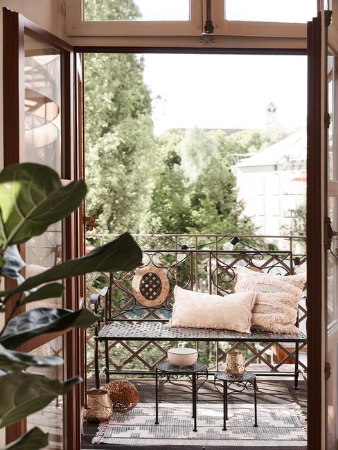 Taras z metalową ławką oraz poduszkami urządzony w stylu boho