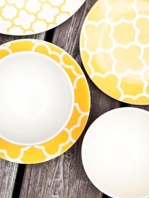 Biało - żółte talerze położone na drewnianym stole