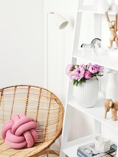 Białe wnętrze z dekoracyjną drabiną z dekoracjami oraz plecionym krzesłem z poduszką supłem