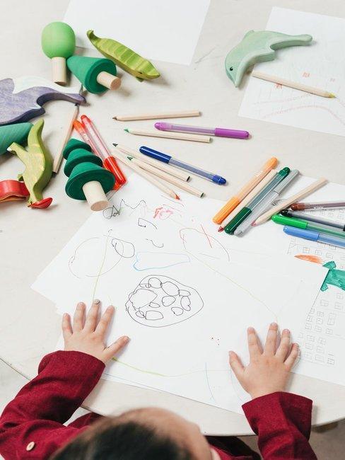 Dziecka siedzące przy stole przed kartką papieru z mazakami oraz kredkami