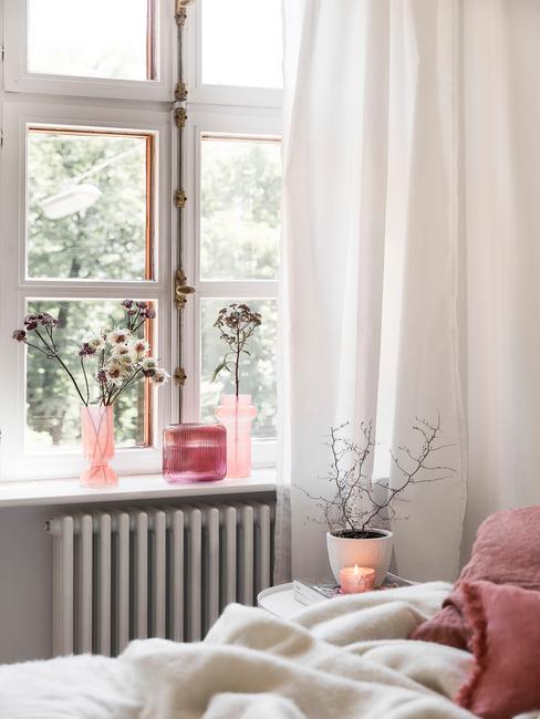 Biała sypialnia z dodatkami w postaci wazonów oraz koca w kolorze millenial pink