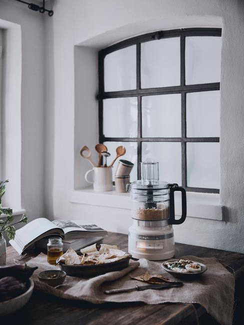 Biała kuchnia z dewnianym stołem oraz czarnymi akcesoriami