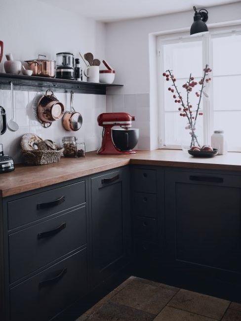 Kuchnia z białą ścianą, czarnymi szafkami oraz dekoracjami i sprzętami kuchennymi