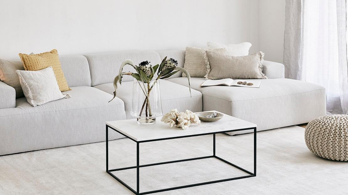 Minimalistisch wohnen helles Wohnzimmer mit großem Sofa und Couchtisch in Marmor
