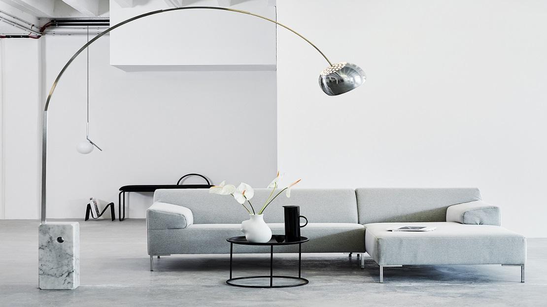 Minimialistisches Wohnzimmer in Grau mit Sofa, großer Stehlampe und kleinem Couchtisch
