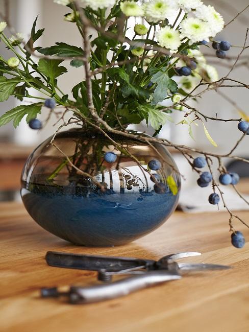 Blaue Vase mit Blumen auf Holztisch