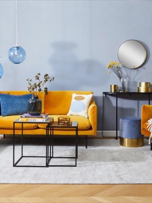 Musztardowa sofa odznaczająca się w salonie utrzymanym w niebieskich tonach