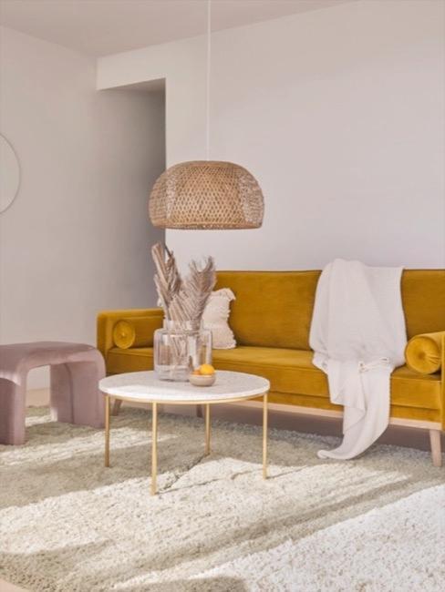 Musztardowa aksamitna sofa w jasnym salonie, ozdobiona dodatkami w naturalnych barwach