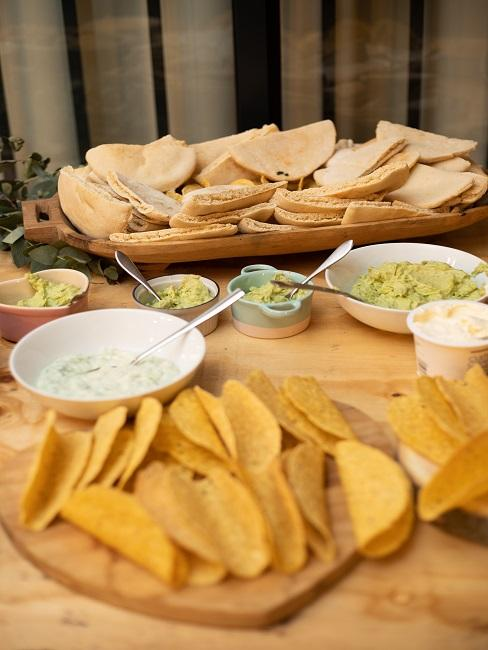 Tisch mit Brot, verschiedenen Dips und Tacos