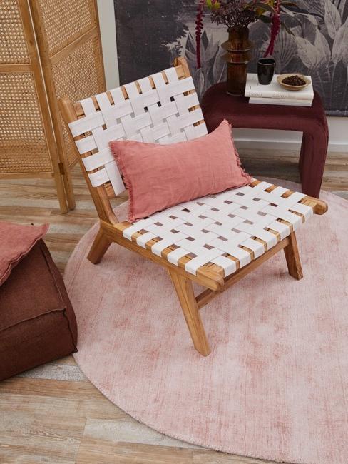 Holzsessel in cremfarben mit Rosa Kissen auf rosa Teppich