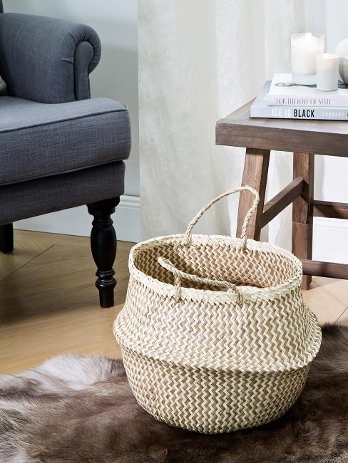 Korb neben einem grauen Sessel und Holzbeistelltisch mit Büchern
