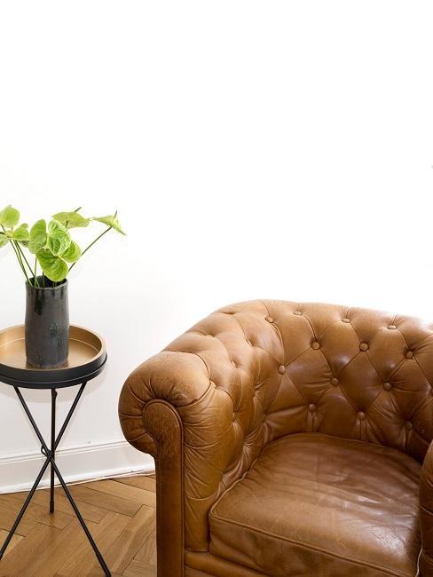 Brauner Vintage Ledersessel neben einem kleinen Beistelltisch mit Pflanzendeko