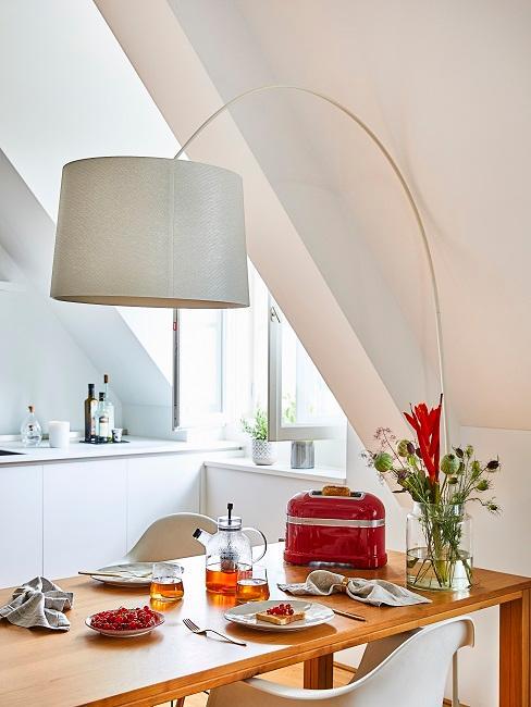 Eine helle Küche mit Dachschräge, einem Holztisch, einer Stehlampe über dem Tisch und schönem Geschirr und Besteck