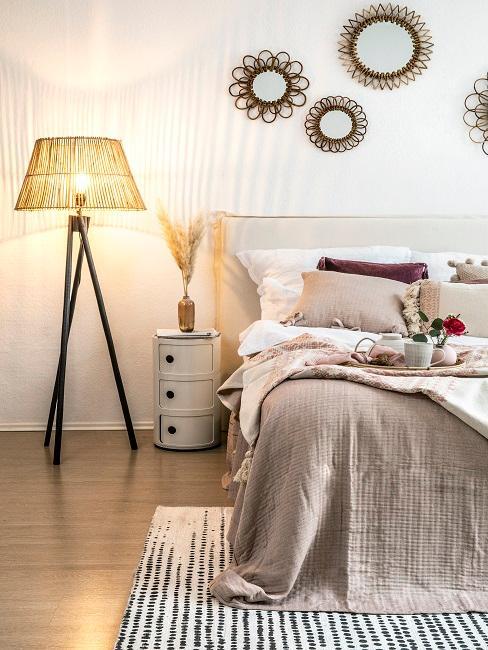 Bett im Schlafzimmer miit Naturfarben und Deko, dazu viele dekorative Spiegel über dem Bettkopf