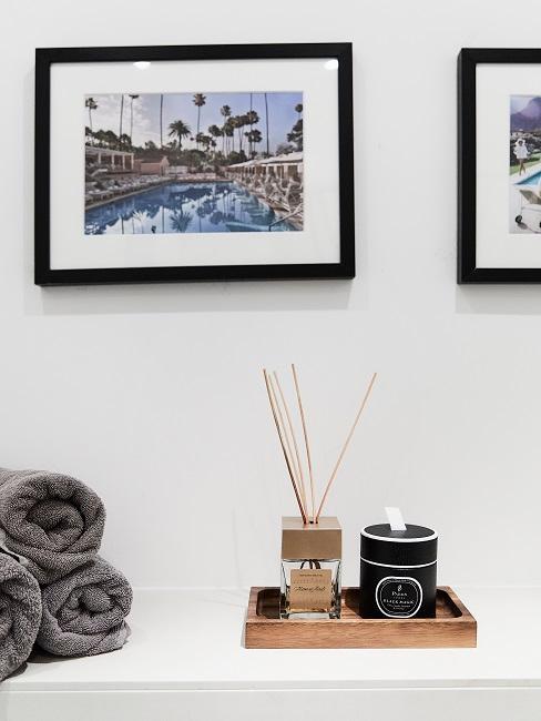 Ablage in einem Bad mit einerm Tablett mit Raumduft und Duftkerze, gerollten Handtüchern und darüber Wandbildern als Deko