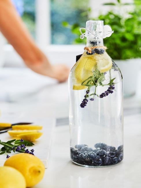Eine Flasche it Wasser und Obst gefüllt als Deko in der Küche