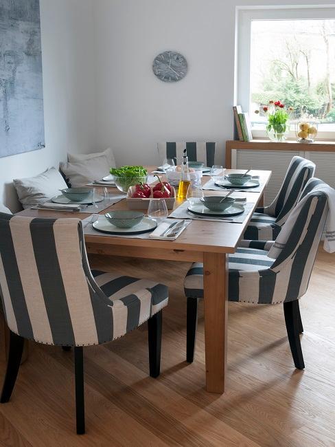 Landhaus Esszimmer mit Holztisch und gestreiften Polsterstühlen
