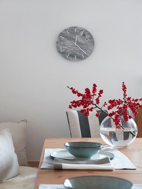 Geschirr auf Holtisch und Vase mit roter Pflanze