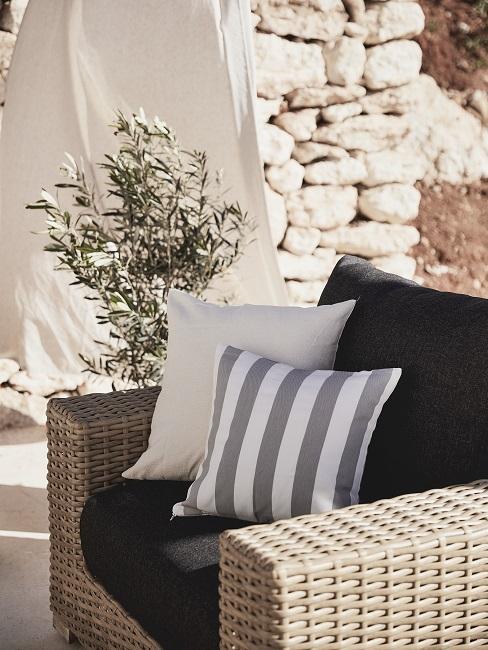 Lounge Sessel aus Rattan mit schwarzem Polster undDekokissen