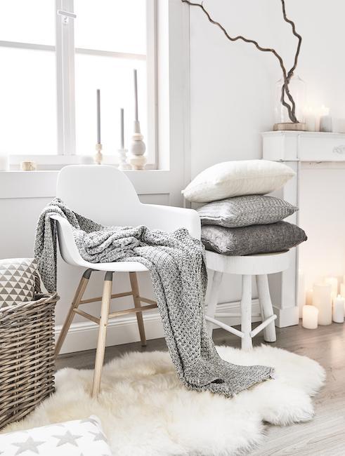 Witte stoel in Scandi stijl met houten frame en bijzettafel gedecoreerd met kussens en deken in grijstinten