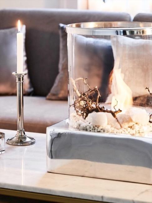 Grijze fluwelen bank met bontkussens op de achtergrond, marmeren salontafel met zilveren lantaarn en zilveren kandelaars aan de voorkant.