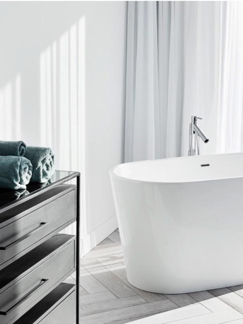 Bañera de estilo moderno con cómoda negra con toallas verdes