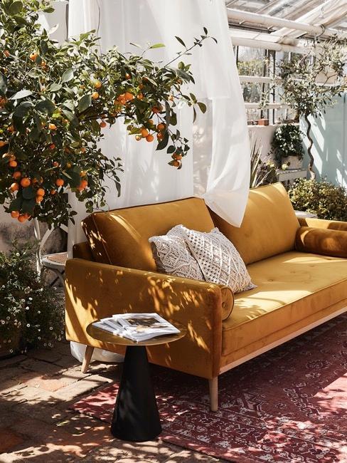 Mosterdkleurige zitbank in de woonkamer met decoratie