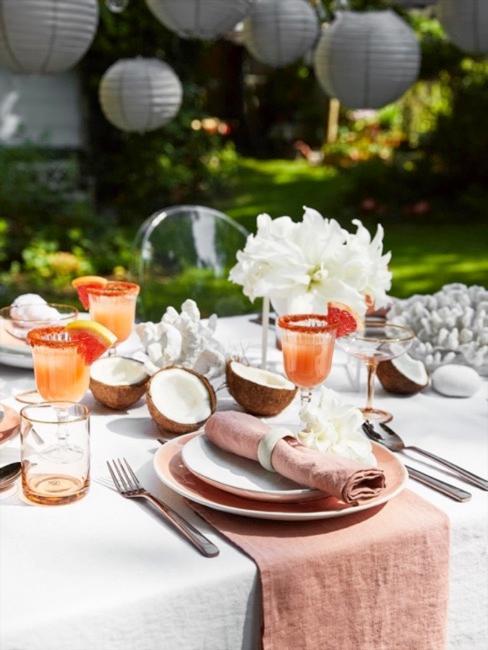 Close-up van een gedekte feesttafel in de tuin met slingers