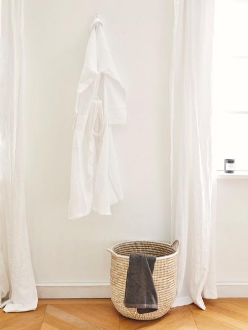 Habitación del baño con albornoz blanco y cesta de mimbre para la ropa sucia