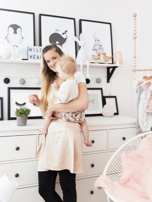 Moeder met kind in babykamer met decoratie