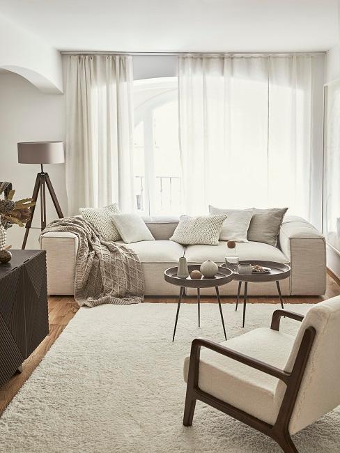 Woonkamer met wit teddy tapijt, hoeklamp, witte gordijnen en sttoel
