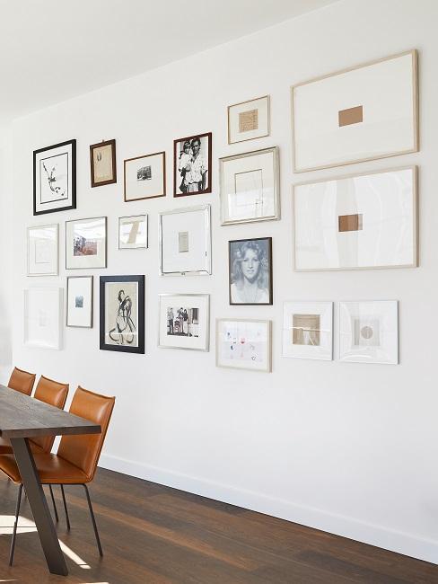 Viele Bilder als große Wandcollage in einem Büro hinter einem Besprechungstisch mit Stühlen
