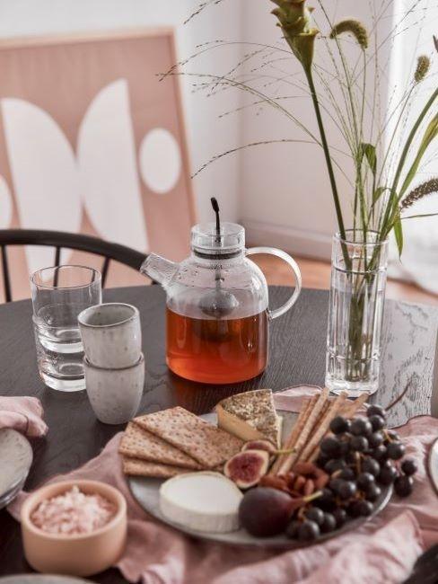 Desayuno sobre una mesa, con tetera de cristal, vasos y tazas, jarrón de flores y una bandeja con fruta, queso y tostadas