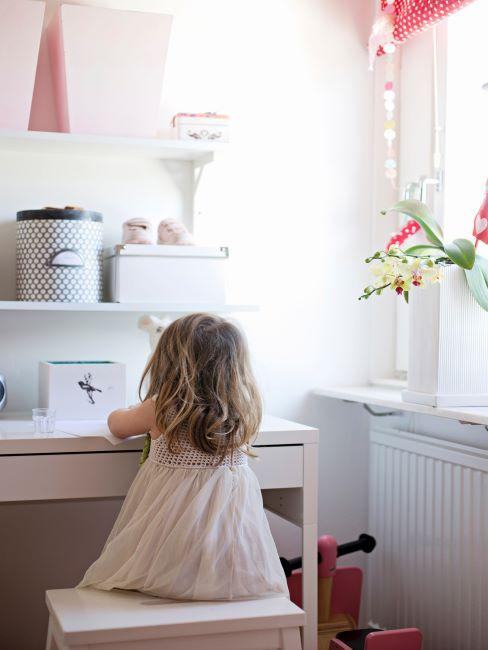 Petite fille assise à son bureau blanc avec boîtes de rangement blanches et fleurs dans un vase blanc